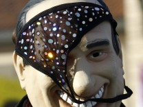 A protester wears a mask of Italian Prime Minister Silvio Berlusconi with a pair of knickers on it during a protest in Arcore