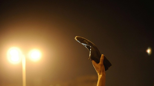 A protester waves a shoe, a sign of disrespect, in Tahrir Square to Egyptian President Hosni Mubarak's televised speech in Cairo
