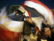 An Egyptian man waves Egyptian flags inside Tahrir Square after the announcement of Egyptian President Hosni Mubarak's resignation in Cairo