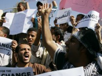 Anti-government protesters shout slogans during a protest outside Sanaa University