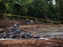 Ecuadorean workers clean up an oil waste pit owned by state petroleum company Petroecuador in Shushufindi