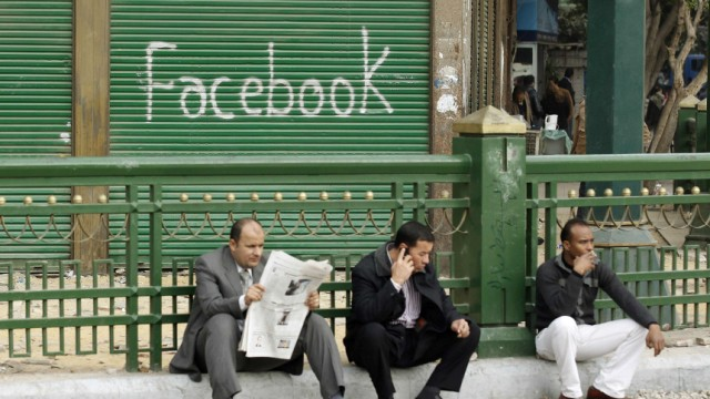 Anti-government protesters sit next to a 'Facebook' graffiti sign during demonstrations inside Tahrir Square in Cairo