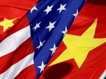 The national flags of the U.S. and China wave in front of an international hotel in Beijing