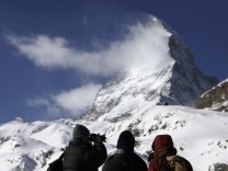 A tourist takes a picture of the Matterhorn mountain at Schwarzsee in the ski resort of Zermatt