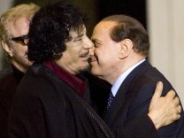 File photo of Gaddafi is greeted by Italy's Prime Minister Silvio Berlusconi in Rome