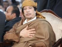Libyan leader Muammar Gaddafi prays during a ceremony marking the