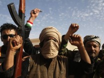 Protesters shout anti-government slogans near a bombed ammunitions store in Tobruk