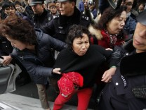 A woman is arrested by police near the Peace Cinema in downtown Shanghai