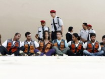 Security guards watch over Greenpeace activists arrested for raising inflatable model of wind turbine in Brasilia