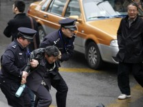 Police arrest a man in front of the Peace Cinema in downtown Shanghai, after calls for a 'Jasmine Revolution' protest, organised through the internet