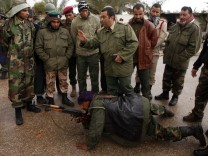 Rebel army officers teach the use of a AK-47 to civilians who have volunteered to join the rebel army in Benghazi