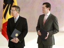 Newly appointed German Defence Minister de Maiziere and former defence minister zu Guttenberg attend a ceremony in presidential residence Bellevue palace in Berlin