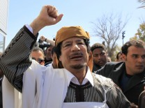 Libyan leader Muammar Gaddafi waves in Tripoli before making a speech