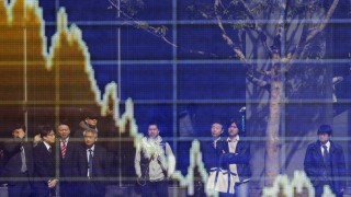People are reflected on an electronic board displaying a graph showing the movement of the Japanese Yen's exchange rate against the U.S. dollar, outside a brokerage in Tokyo