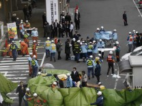 Rescue workers hurry to a building following reports of injuries in Tokyo's financial district after an earthquake off the coast of northern Japan