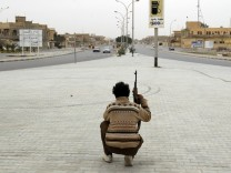 A rebel fighter takes a break as soldiers loyal to Libyan leader Muammar Gaddafi approach Ajdabiyah