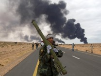 A rebel holds a man-portable air-defense system during clashes with pro-Gaddafi forces between Ras Lanuf  and Bin Jawad