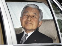 Japanese Emperor Akihito greets people from his limousine after visiting the tomb of his late father Emperor Hirohito at the Musashino Imperial Mausoleum in Tokyo