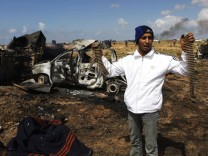 A Libyan youth stands beside the charred body of a Gaddafi loyalist soldier on the outskirts of Benghazi