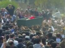 Frame grab of a crowd chanting anti-regime slogans during a funeral procession for a protester killed in Dara