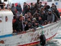 A boat carrying immigrants arrives to the Italian island of Lampe