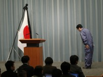 Japan's PM Kan bows to the Japanese flag with a black mourning cloth during a news conference at his official residence in Tokyo