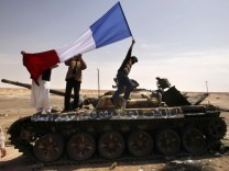 A man waves a French flag on top of a destroyed tank belonging to forces loyal to Libyan leader Muammar Gaddafi in Ajdabiyah