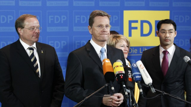 Leader of FDP Westerwelle and party fellows Roesler and Niebel react after hearing first exit polls for Baden-Wuerttemberg and Rhineland-Palatinate state election at party headquarters in Berlin