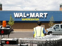 A worker brings carts back into a Walmart store in Westminster