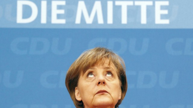German Chancellor and leader of CDUMerkel looks up during news conference after party meeting in Berlin