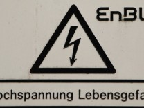 A sign under the logo of German energy provider 'EnBW' reads 'high voltage - life dangerous', on a power line post next to the nuclear power plant in Phillipsburg