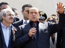 Italian PM Berlusconi speaks after arriving at at the southern Italian island of Lampedusa