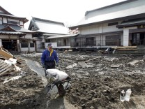 A man helps clear rubbish and mud from a Buddhist temple inundate
