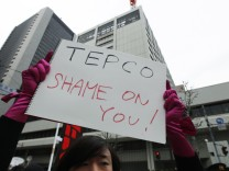 An anti-nuclear protester holds a sign in front of TEPCO's headquarters in Tokyo
