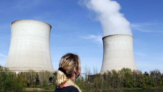 A woman looks at cooling towers of France's Electricite de France nuclear power station in Saint Laurent, Central France