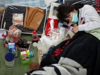 A woman looks at her mobile phone as she rests at an evacuation centre for people affected by the March 11 earthquake and tsunami in Ishinomaki