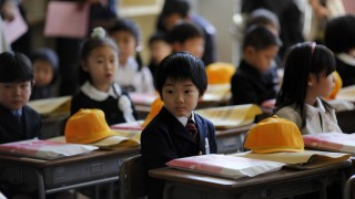 Children sit inside a classroom on their first day of school at Shimizu elementary school in Fukushima