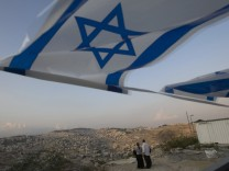 Israeli flag waves near a site where Jewish settlers hope to expand an enclave near Jabal Mukaber