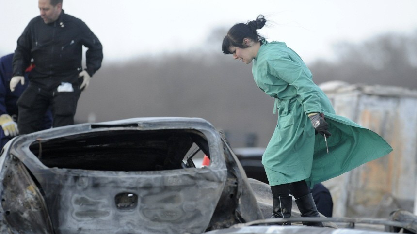 A forensic expert examines burnt cars on the motorway A 19 near eastern German village of Kavelstorf