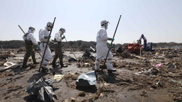 Police officers search for bodies at a destroyed area in Minamisoma