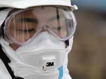 A police officer in a protective suit observes a moment of silence for those who were killed by the March 11 earthquake and tsunami, as they search for bodies at a destroyed area in Minamisoma, Fukushima prefecture