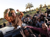 Libyan leader Muammar Gaddafi waves from a car in the compound of Bab Al Azizia in Tripoli