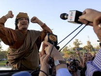 Libyan leader Muammar Gaddafi gestures, as he is surrounded by members of the media, after a meeting with a delegation of five African leaders at his Bab al-Aziziyah compound in Tripoli
