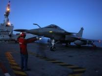 Flight deck crew direct a Rafale fighter jet aboard the Charles de Gaulle aircraft carrier