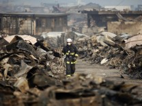 A Japanese rescue worker walks through a destroyed residential area of tsunami-hit Otsuchi