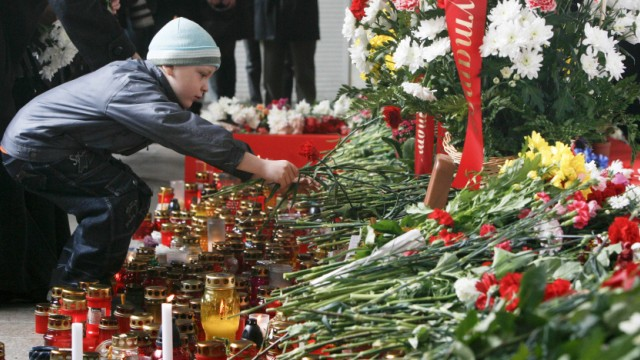 A boy places flowers at the entrance to the Oktyabrskaya metro station in Minsk