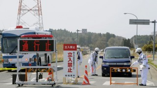 Residents speak to police officers as they leave for Yamagata Prefecture from Minamisoma