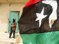 A rebel fighter stands guard behind a Kingdom of Libya flag at Dehiba
