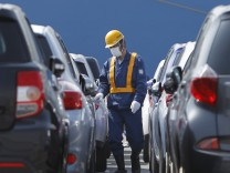 Worker walks among newly produced Toyota cars to drive to a cargo ship at Sendai port in Sendai