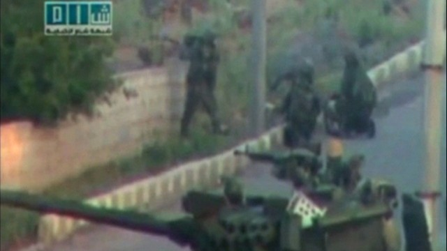 Soldiers take up position near a tank on a street in a location given as Deraa in this still image taken from amateur video